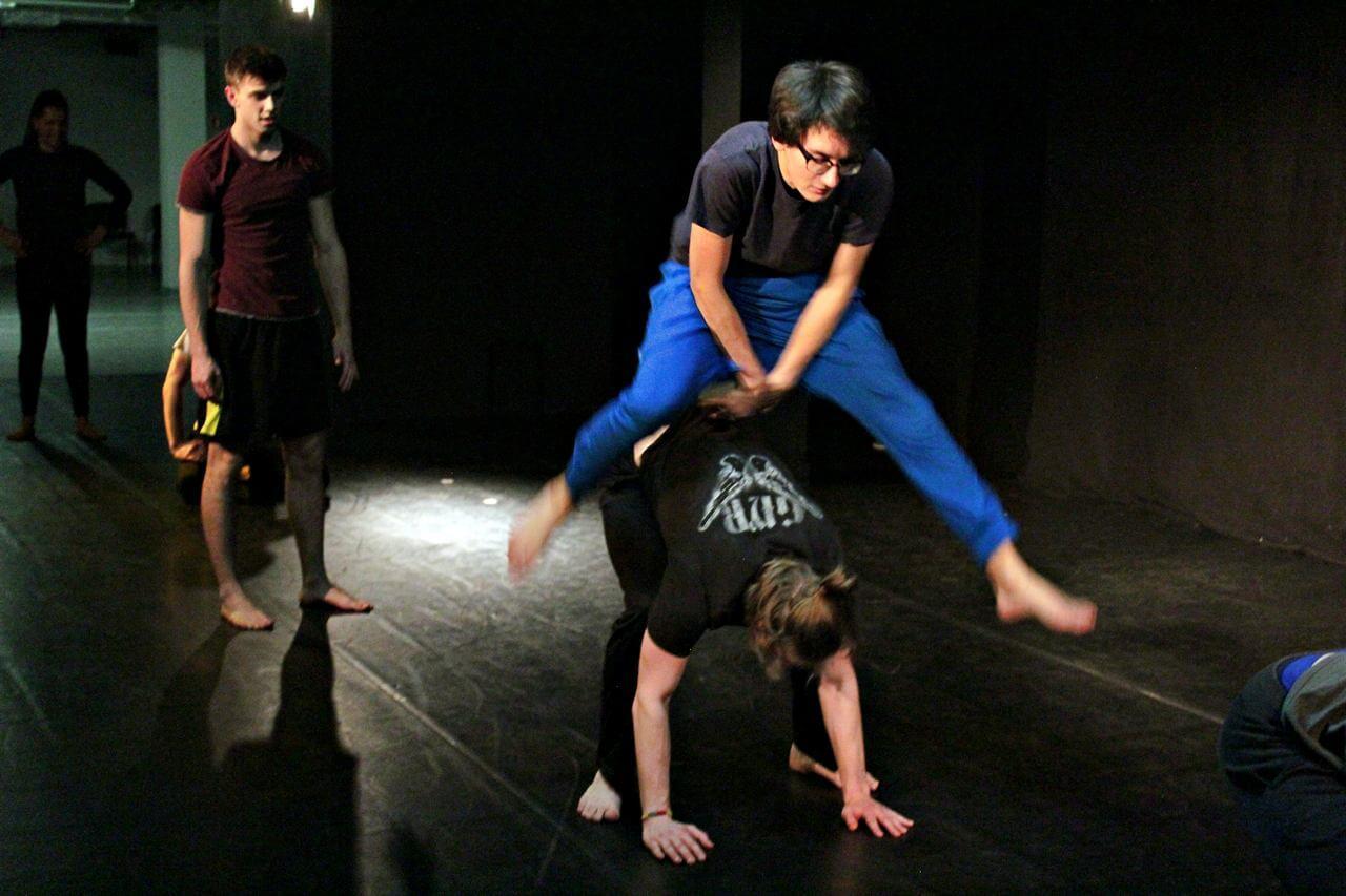 Zdjęcie z projektu Teatr Młodych. Uczestnicy ćwiczą na sali teatralnej. Chłopak w niebieskich spodniach, przeskakuje okrakiem drugiego, który się pochyla.