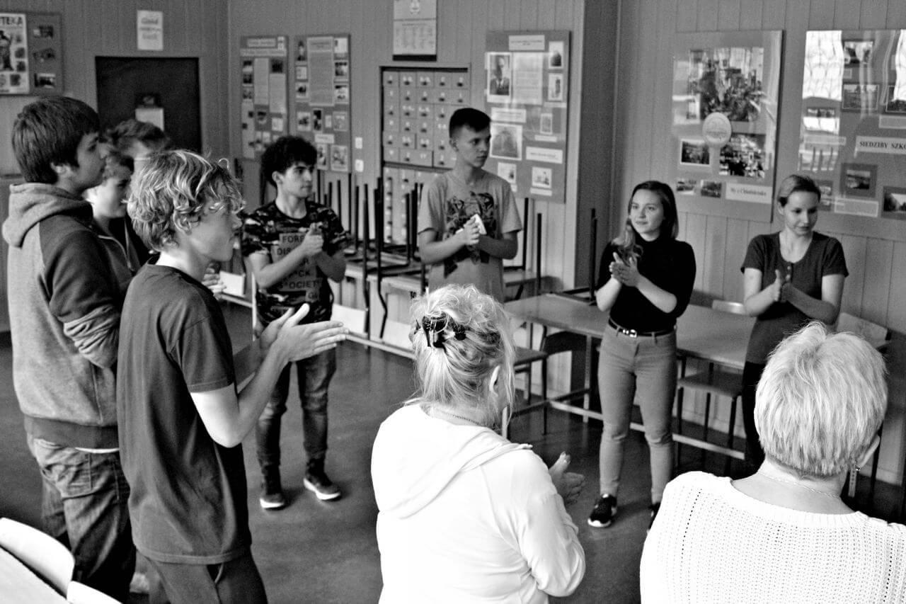 Zdjęcie z projektu Dachy nad Pekinem. Grupa uczestników w róznym wieku stoi w okregu i klaszcze w ręcę. Zdjęcie w szkolnej klasie.