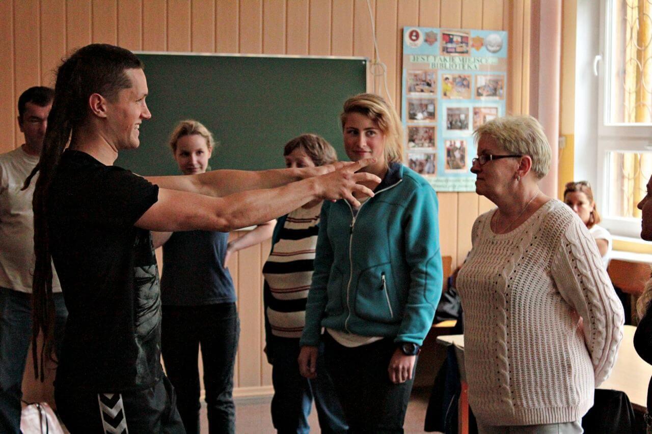 Zdjęcie z projektu Dachy nad Pekinem. Grupa uczestników w róznym wieku w klasie. instruktor wyciaga ręce w kieruku jednej z uczestniczek.