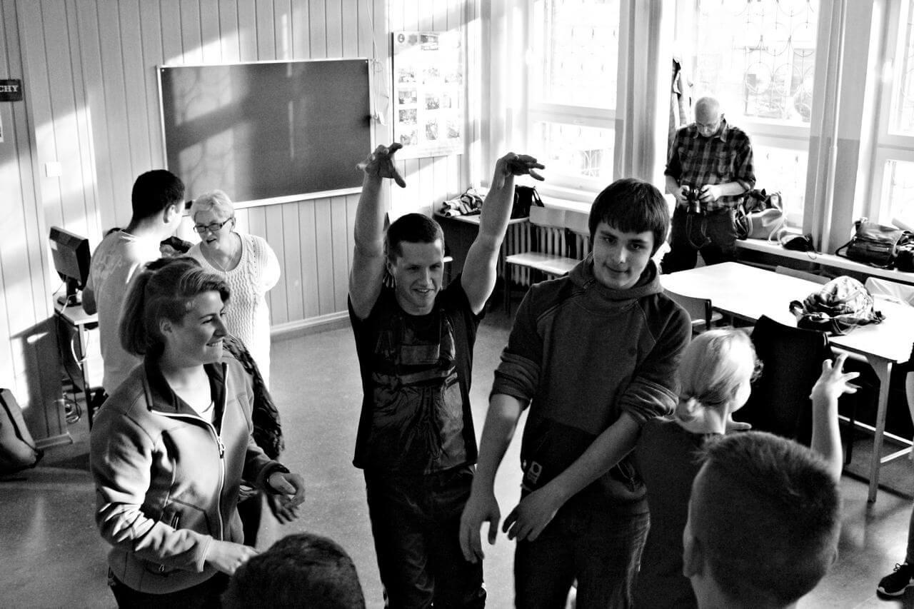 Zdjęcie z projektu Dachy nad Pekinem. Grupa uczestników w róznym wieku w szkolnej klasie. Syoja w kręgu, instruktor podnosi ręce.