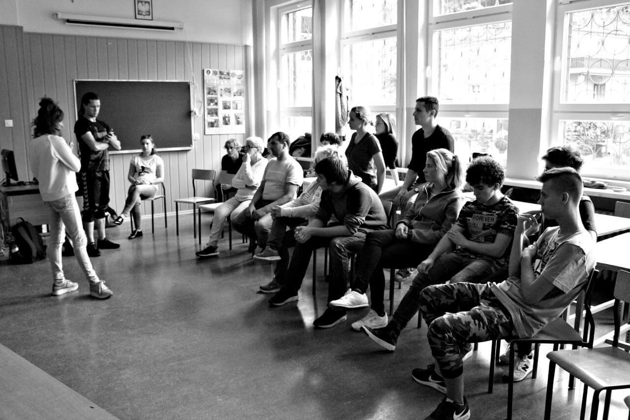 Zdjęcie z projektu Dachy nad Pekinem. Grupa uczestników w róznym wieku w szkolnej klasie. Siedza na kszesełkach na wprost instruktorów.