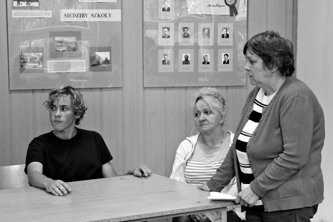 Zdjęcie z projektu Dachy nad Pekinem. Troje uczestników przy stole. Młody człowiek siedzi przy stole z lewej strony, po prawo dwie starsze uczestniczki, jedna siedzi druga stoi.