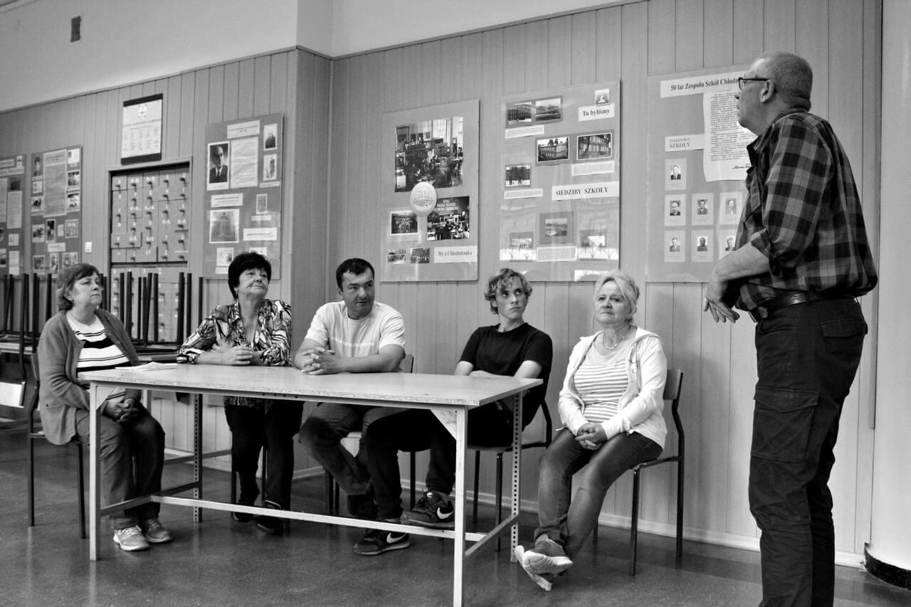 Zdjęcie z projektu Dachy nad Pekinem. Pieciu uczestników siedzi za stołem. Po prawo mężczyzna do nich przemawia.