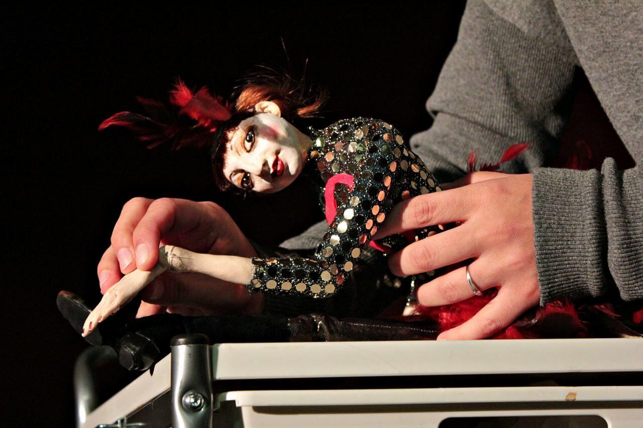 Zdjecie do spektaklu Abecadło. Na zdjęciu lalka tancerka, ubrana w strój z cekinów i pióra na głowie. lalka w szpagacie.