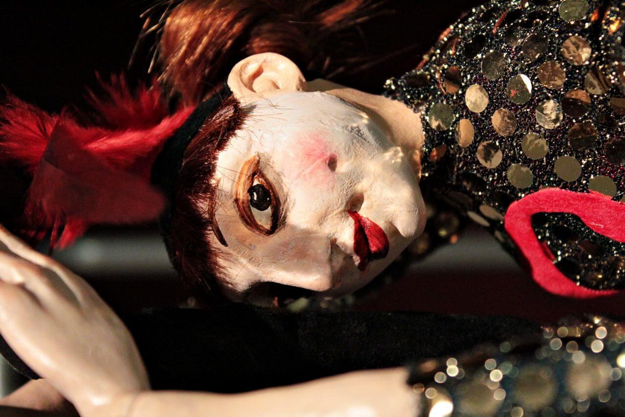 Zdjecie do spektaklu Abecadło. Na zdjęciu lalka tancerka, ubrana w strój z cekinów i pióra na głowie. Duze zblizenie na twarz.