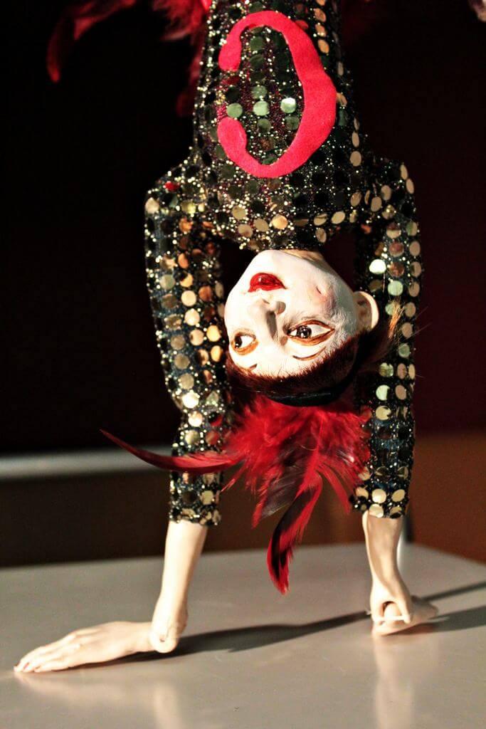 Zdjecie do spektaklu Abecadło. Na zdjęciu lalka tancerka, ubrana w strój z cekinów i pióra na głowie. Lalka stoi na rękach.