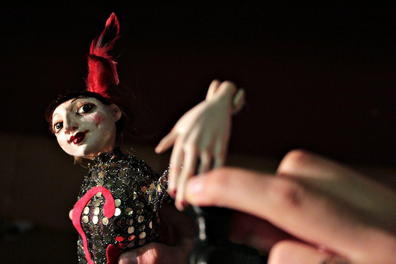 Zdjecie do spektaklu Abecadło. Na zdjęciu lalka tancerka, ubrana w strój z cekinów i pióra na głowie. Lalka z wysunieta do przodu dłonią.
