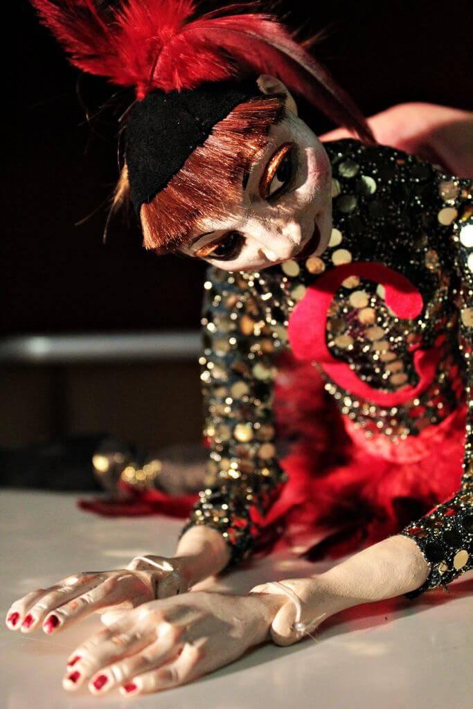 Zdjecie do spektaklu Abecadło. Na zdjęciu lalka tancerka, ubrana w strój z cekinów i pióra na głowie. Pochylona z rękami przed sobą.