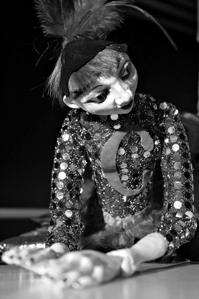 Zdjecie do spektaklu Abecadło. Na zdjęciu lalka tancerka, ubrana w strój z cekinów i pióra na głowie. Z rękoma przed sobą.