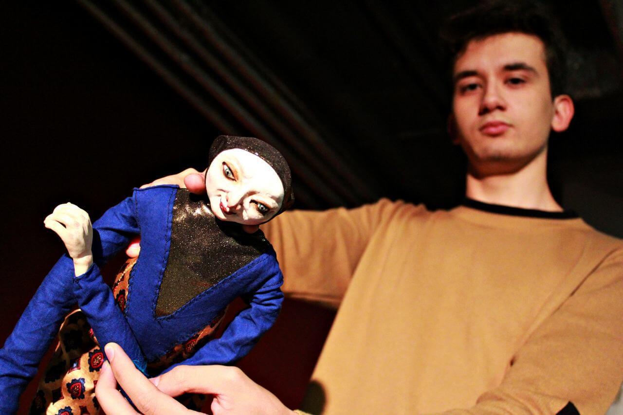 Zdjecie do spektaklu Abecadło. na zdjęciu aktor w bezowej bluzie animuje niebieską lalkę.