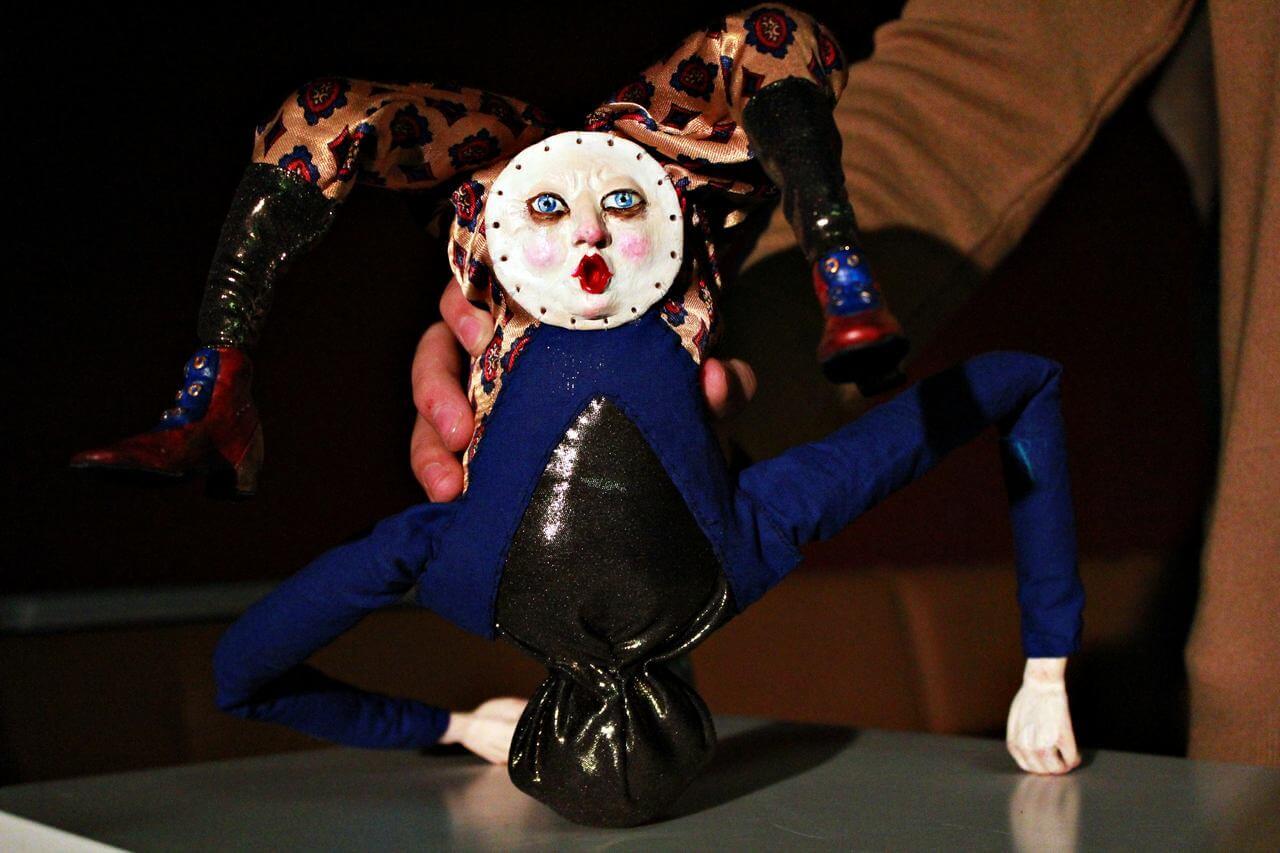 Zdjecie do spektaklu Abecadło. Na zdjęciu lalka ala błazen. Posiadająca okrągłą twarz na plecach.
