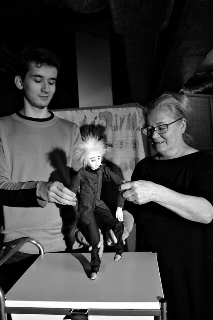 Zdjecie do spektaklu Abecadło. Na zdjęciu dwoje aktorów animuje lalkę - Alberta Einsteina.