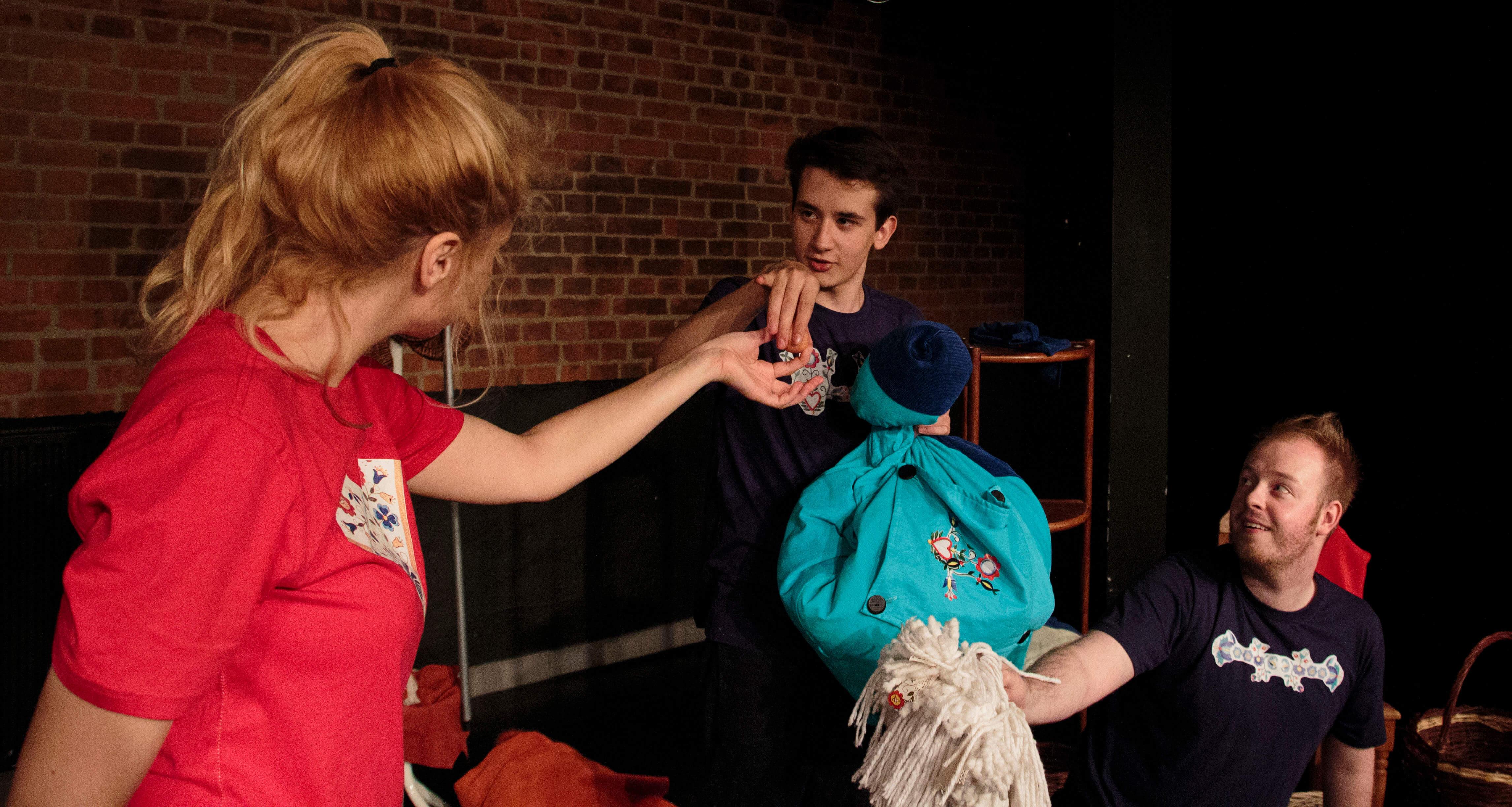 Zdjęcie ze spektaklu Tymoteusz Rym Cim Cim. Trójka aktorów. Aktorka w czerwonej koszulce podaje aktorowi jako. Drugi aktor trzyma mopa.