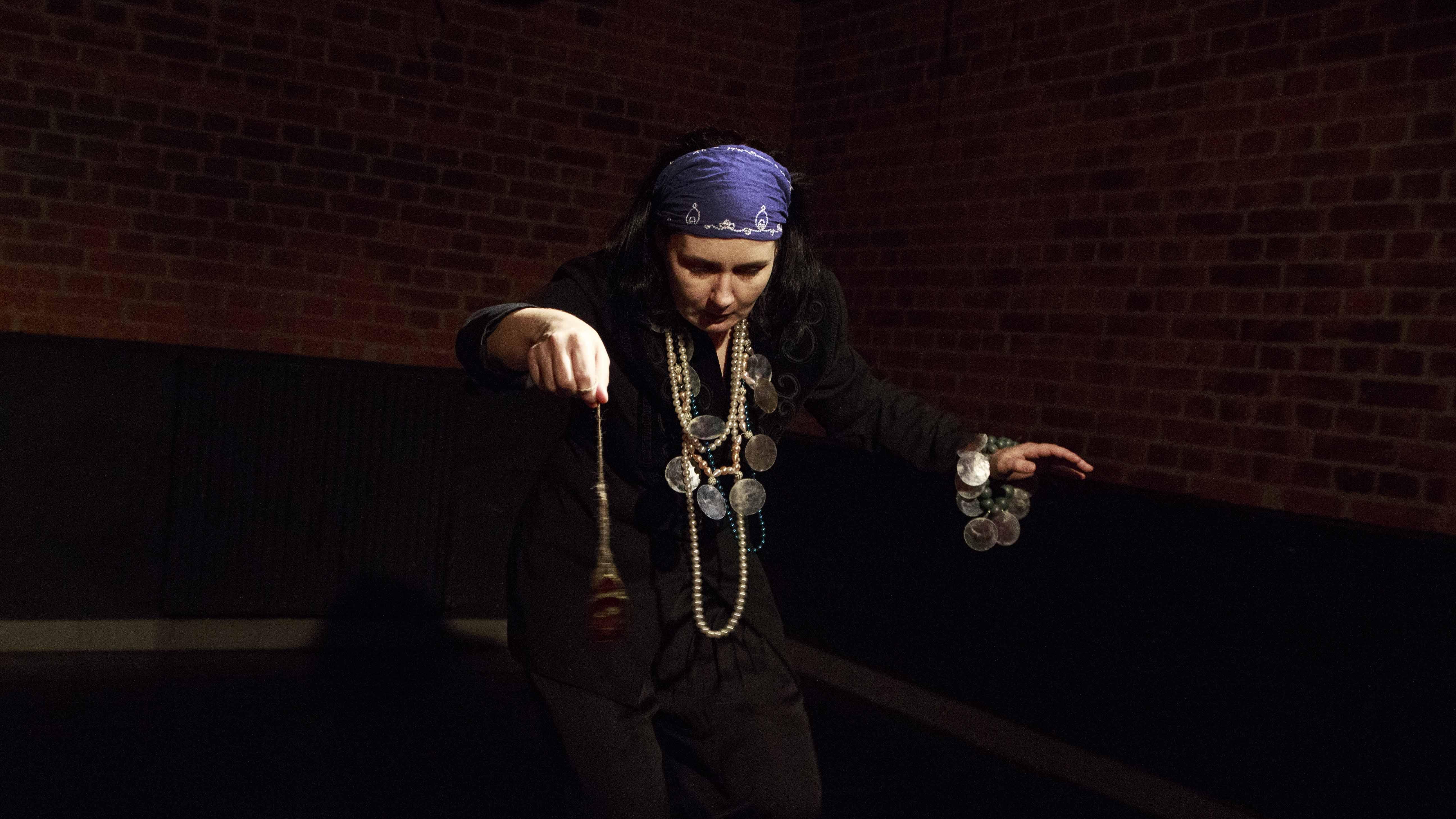Zdjęcie ze spektaklu Dzielnice cudów. Aktorka przebrana za cygankę, trzyma w ręku wahadełko.