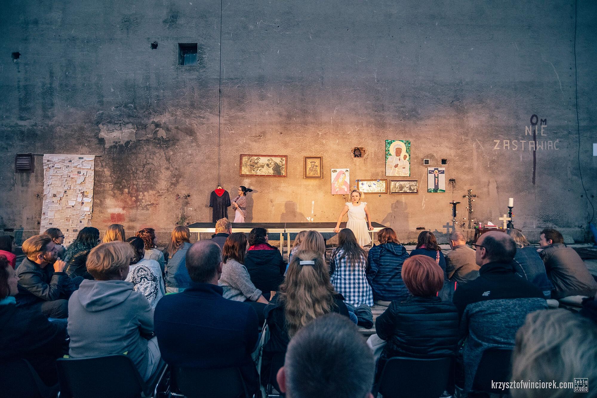 Zdjęcie do spektaklu Kawa, Chleb i ser. Publicznosc zgromadzona przed wysoką brudną ścianą na której wiszą religijne obrazy. W drugim planie 2 aktorki.