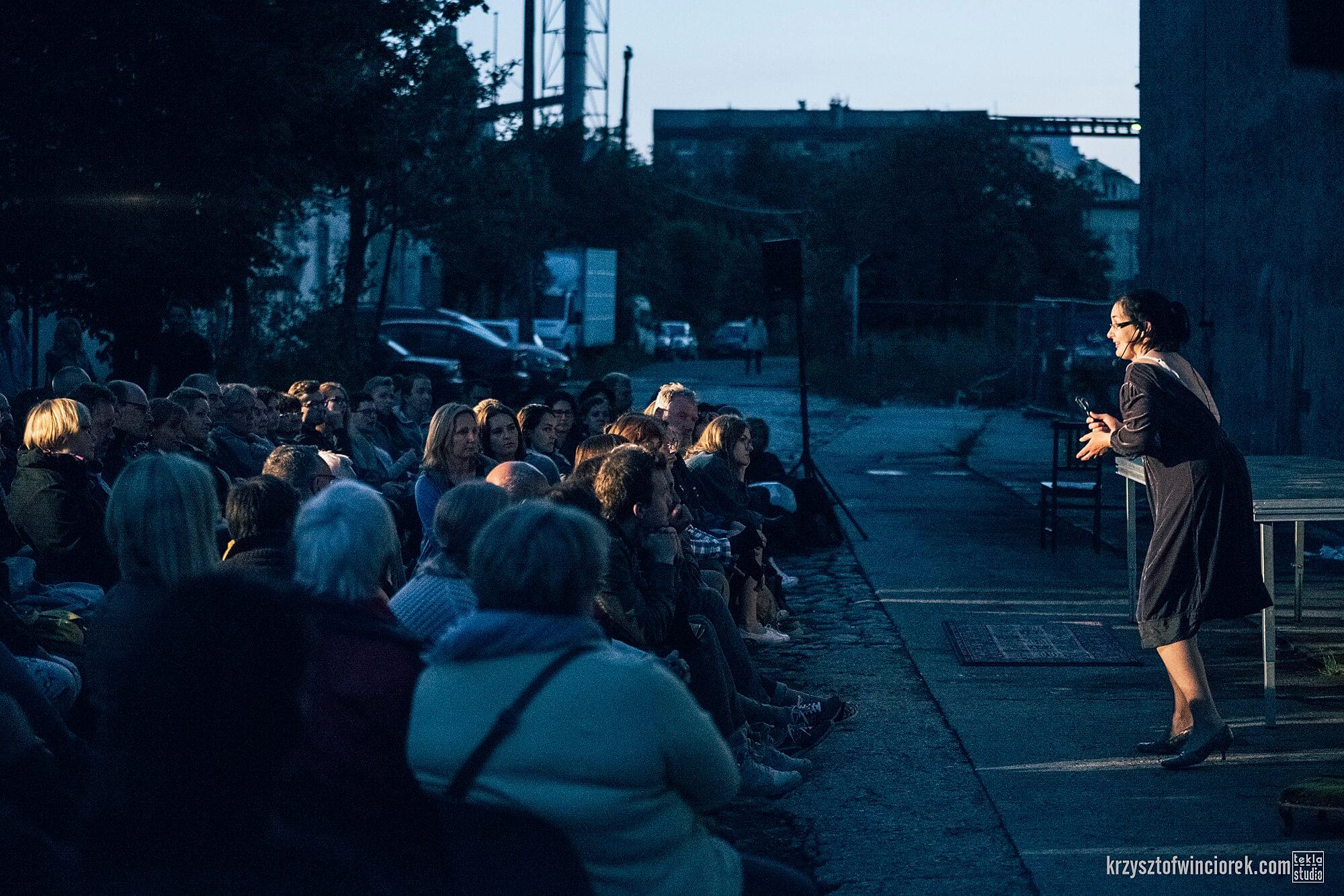 Zdjęcie do spektaklu Kawa, Chleb i ser. Na przeciwko widowni aktorka w czarnej sukience. W tle fabryczne zabudowania