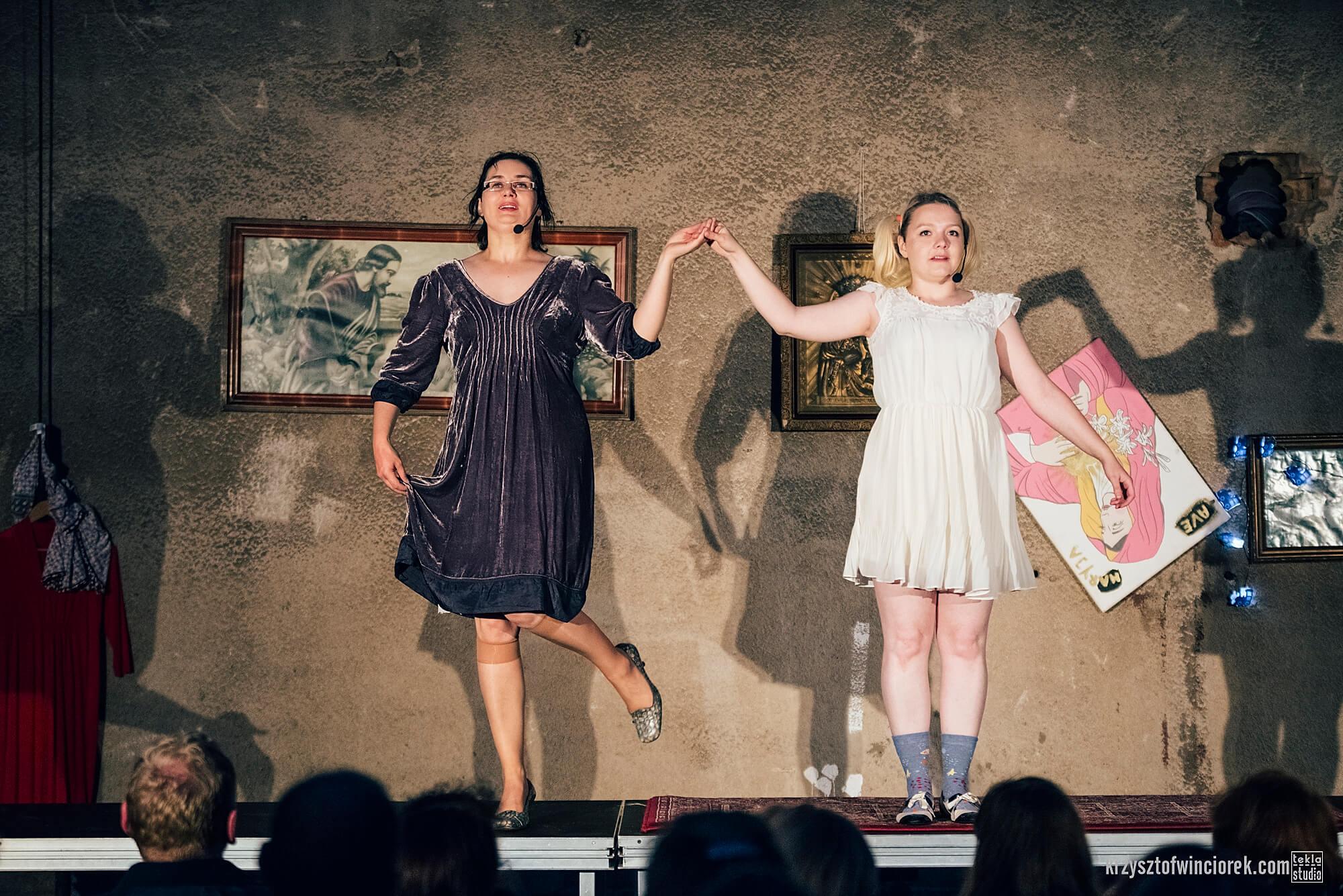 Zdjęcie do spektaklu Kawa, Chleb i ser. Dwie aktorki tanczą na stole przodem do widzów. Trzymają się za rekę. Po lewo aktorka w szarej sukience z uniesiona lekko noga. Po prawo aktorka w białej sukience. na ścianie z tyłu wiszą obrazy religijne.