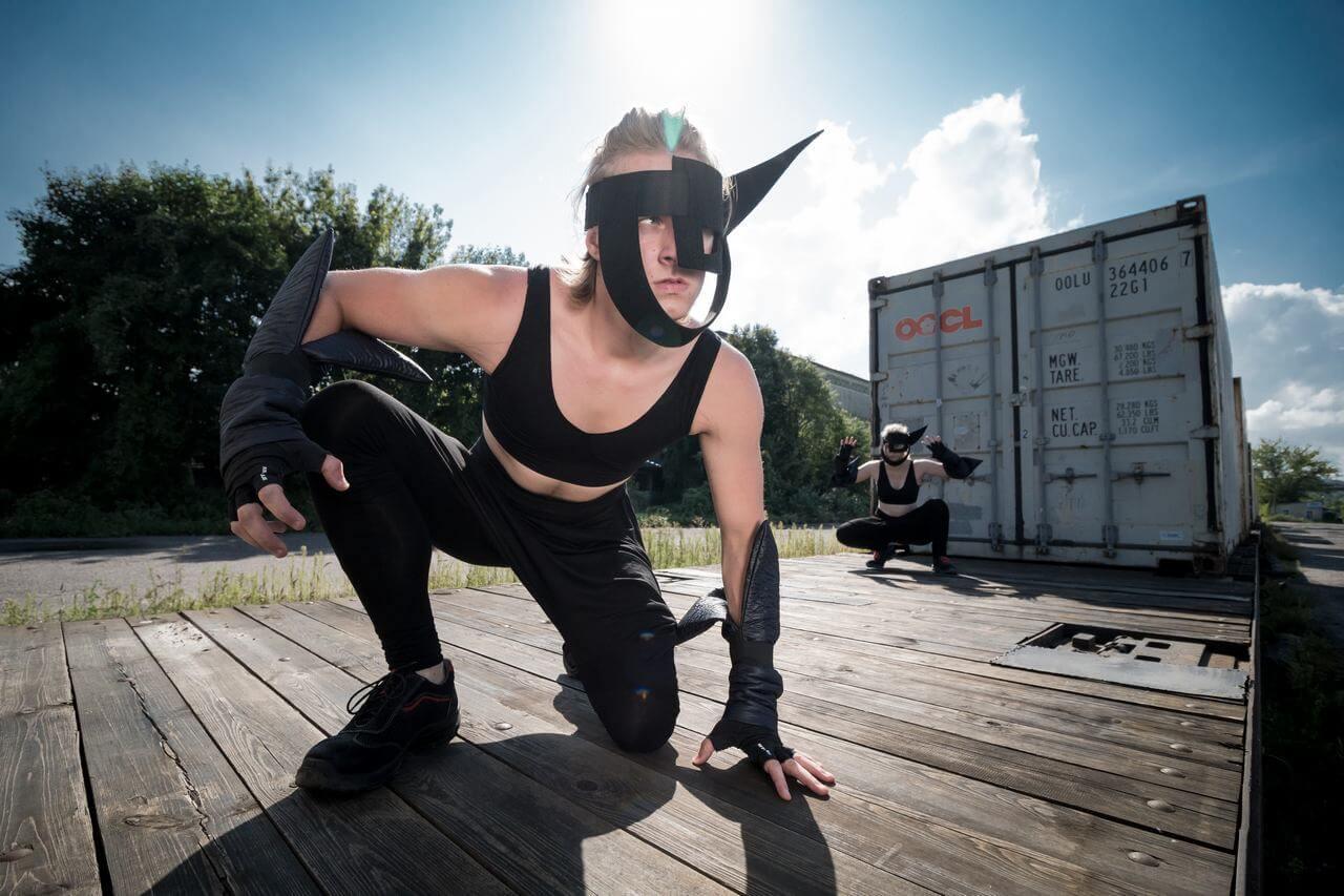Zdjęcie do spektaklu Masska. Aktor w czarnym kostiumie i masce na twarzy, klęczy na platformie wagonu.