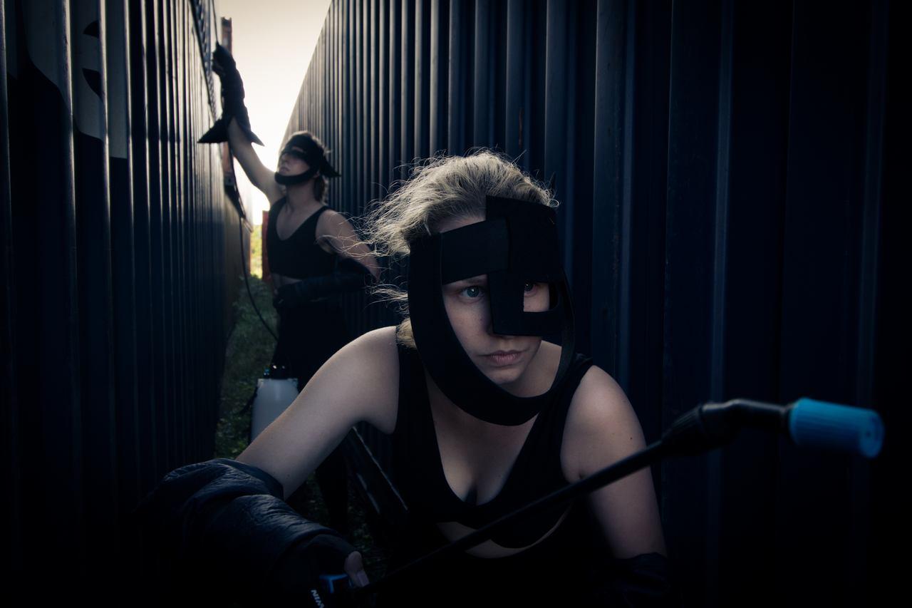 Zdjęcie do spektaklu Masska. Aktorzy ubrani w czarne kostiumy, z czarnymi maskami imitującymi chełmy. Przeciskaja się pomiędzy dwoma kontenerami.