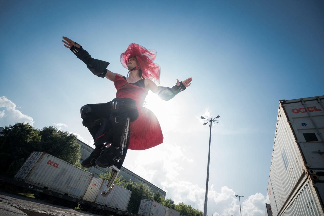 Zdjęcie do spektaklu Masska. Aktor w czerwono czarnym kostiumie skacze na platformie.
