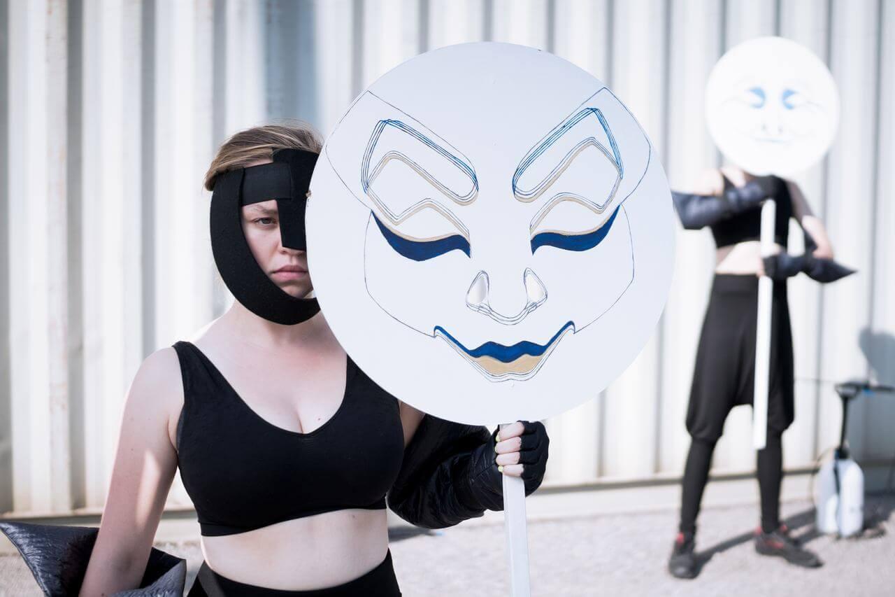 Zdjęcie do spektaklu Masska. Aktorka ubrana w czarny kostium i maskę. Trzyma w rękach duzą, okragłą maskę na kiju. Zakrywa nią sobie połowę twarzy. W tle aktor w podobnej pozie.