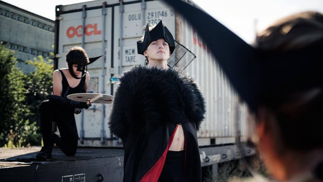Zdjęcie do spektaklu Masska. Aktor w kostiumie z czarnego futra oraz w czarnej koronie na głowie.