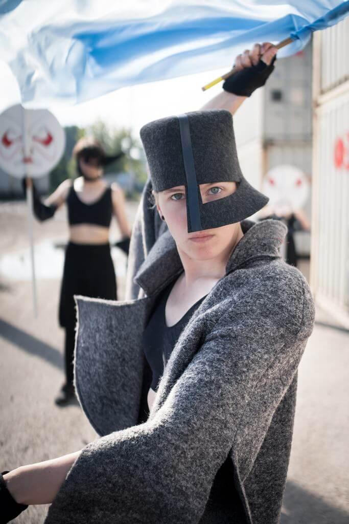 Zdjęcie do spektaklu Masska. Aktorka w szarym kostiumie i czarnej masce na głowie imitującej chełm. W reku wymachuje niebieską flagą.