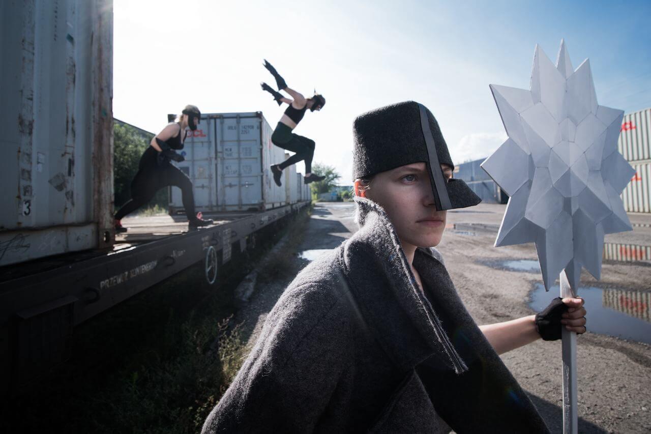 Zdjęcie do spektaklu Masska. Aktorka w szarym kostiumie i z czarną maską imitującą chełm na głowie. Trzyma w reku białą gwiazdę na długim kiju. W tele dwójka aktorów zeskakuje z platformy.