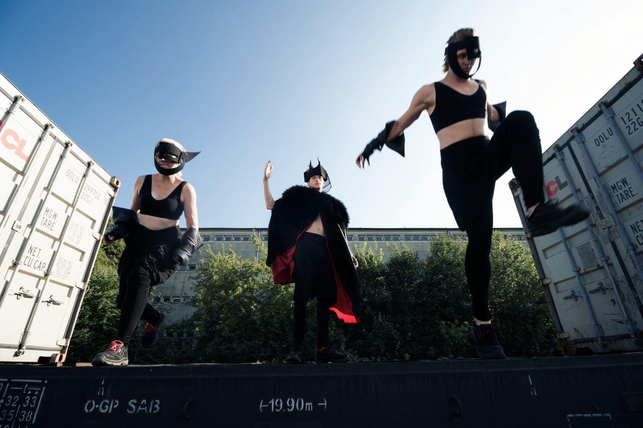 Zdjęcie do spektaklu Masska. Trójka aktorów w dziwnych kostiumach na platformie.