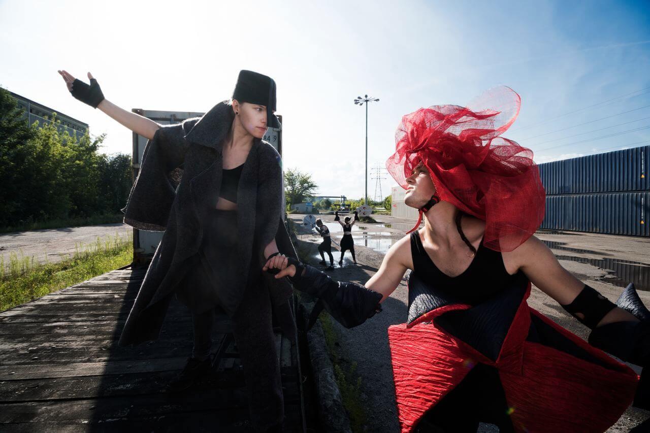 Zdjęcie do spektaklu Masska. Aktorka w czarnym kostiumie i aktor w czarno czerwonym kostiumie trzymają się za rękę. Zdjęcie na platwormie wagonu kolejowego.
