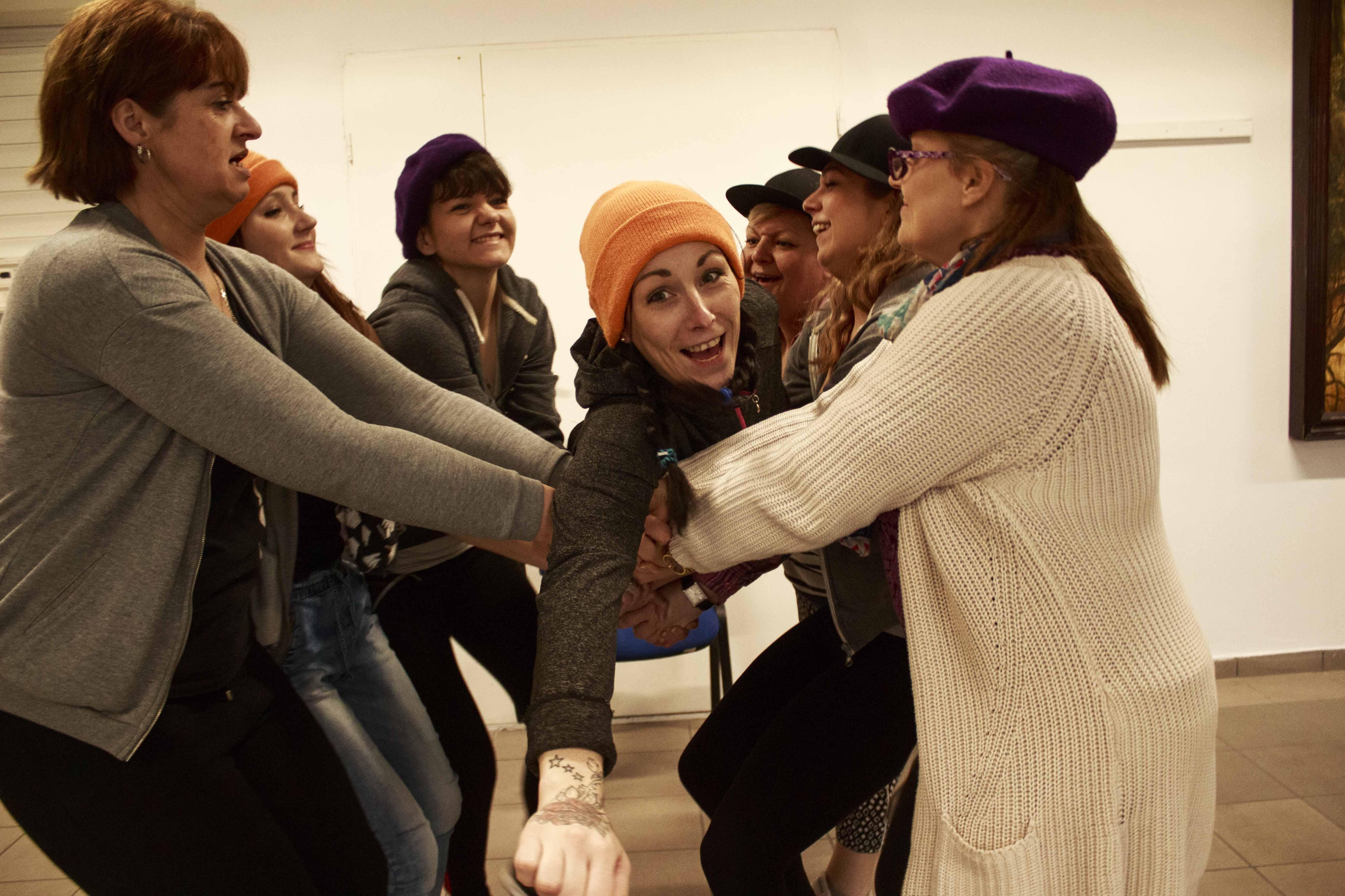 Kilka kobiet trzyma się za ręce w dwóch rzędach na przeciwko. Na ich rękach lezy dziewczyna w pomarańczowej czapce.