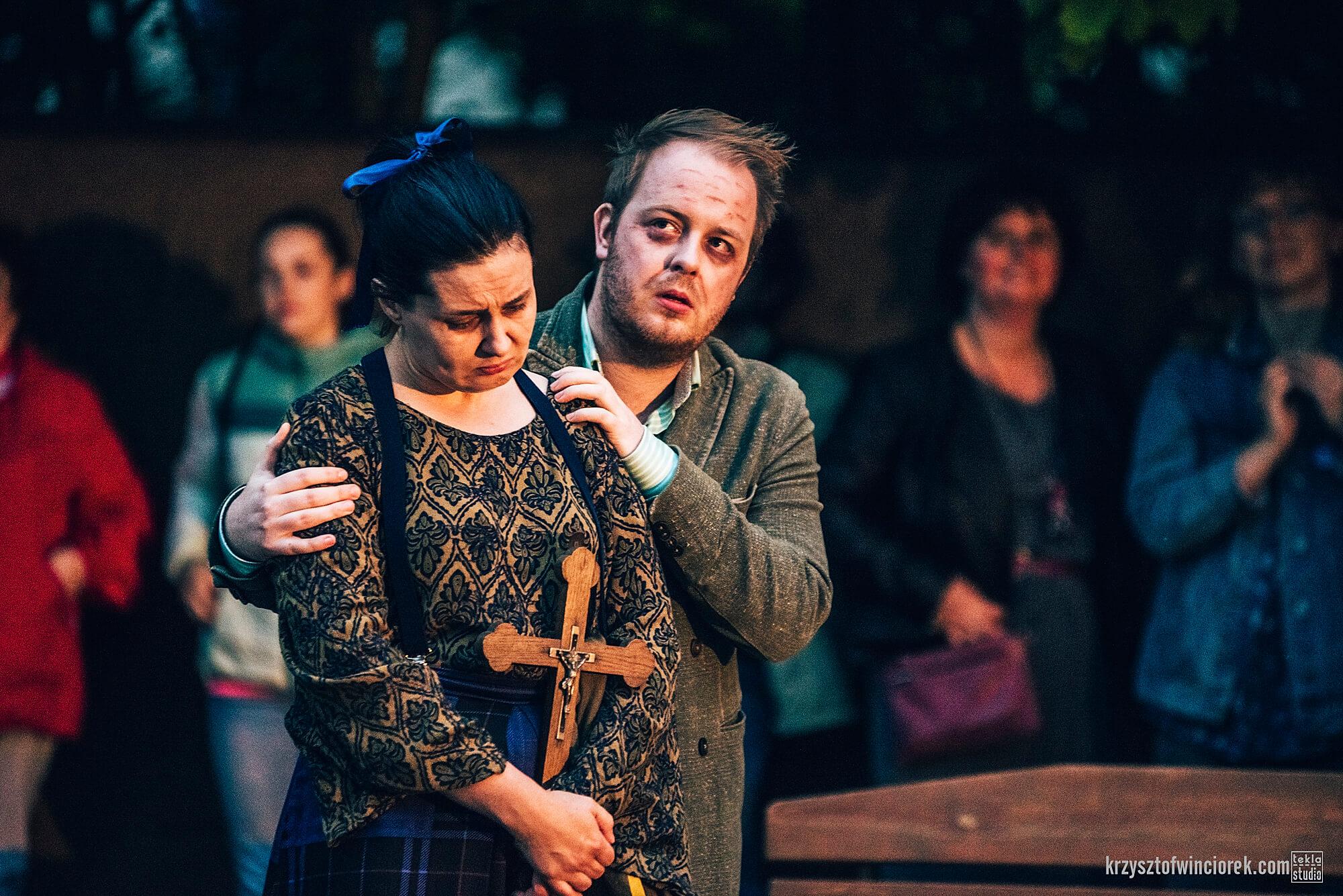 Zdjęcie z festiwalu Pociąg do miasta. Aktorka ucharekteryzowana na staro, z pochylona głową trzyma krzyż. Za nią aktor trzyma ją za ramiona.