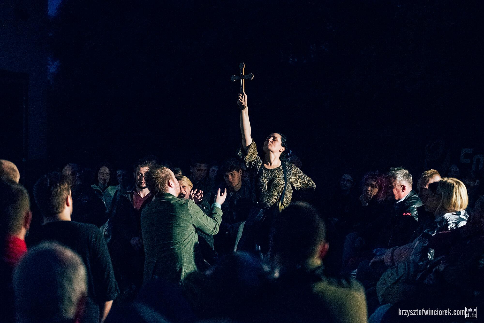Zdjęcie z festiwalu Pociąg do miasta. Pośrodku tłumu aktorka podnosi rękę w której trzyma krzyż.