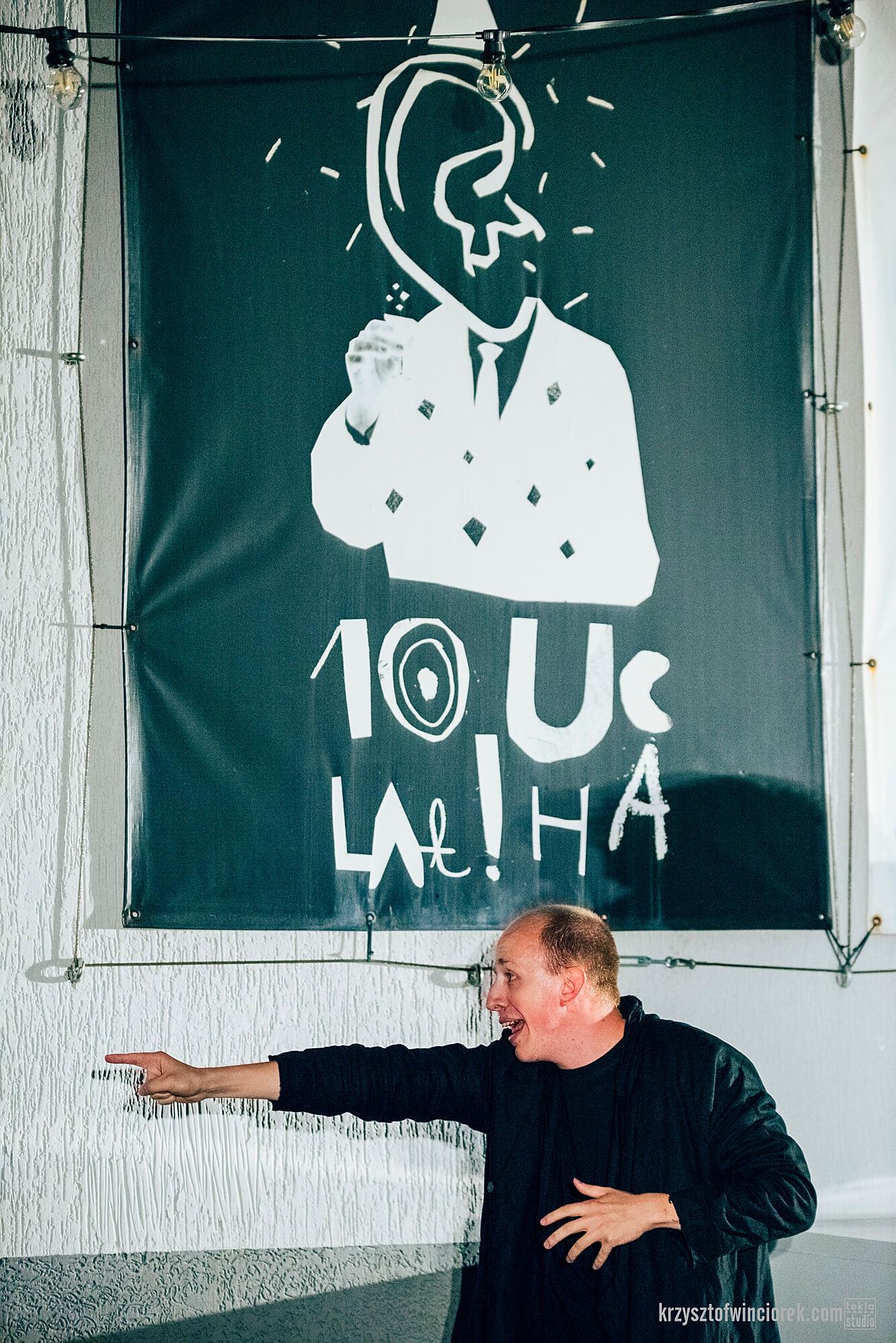 Zdjęcie z festiwalu Pociąg do miasta. Aktor z wyciągniętą w lewo reką i wskazującym palcem. Za nim na ścianie baner z napisem 10 lat ucha.