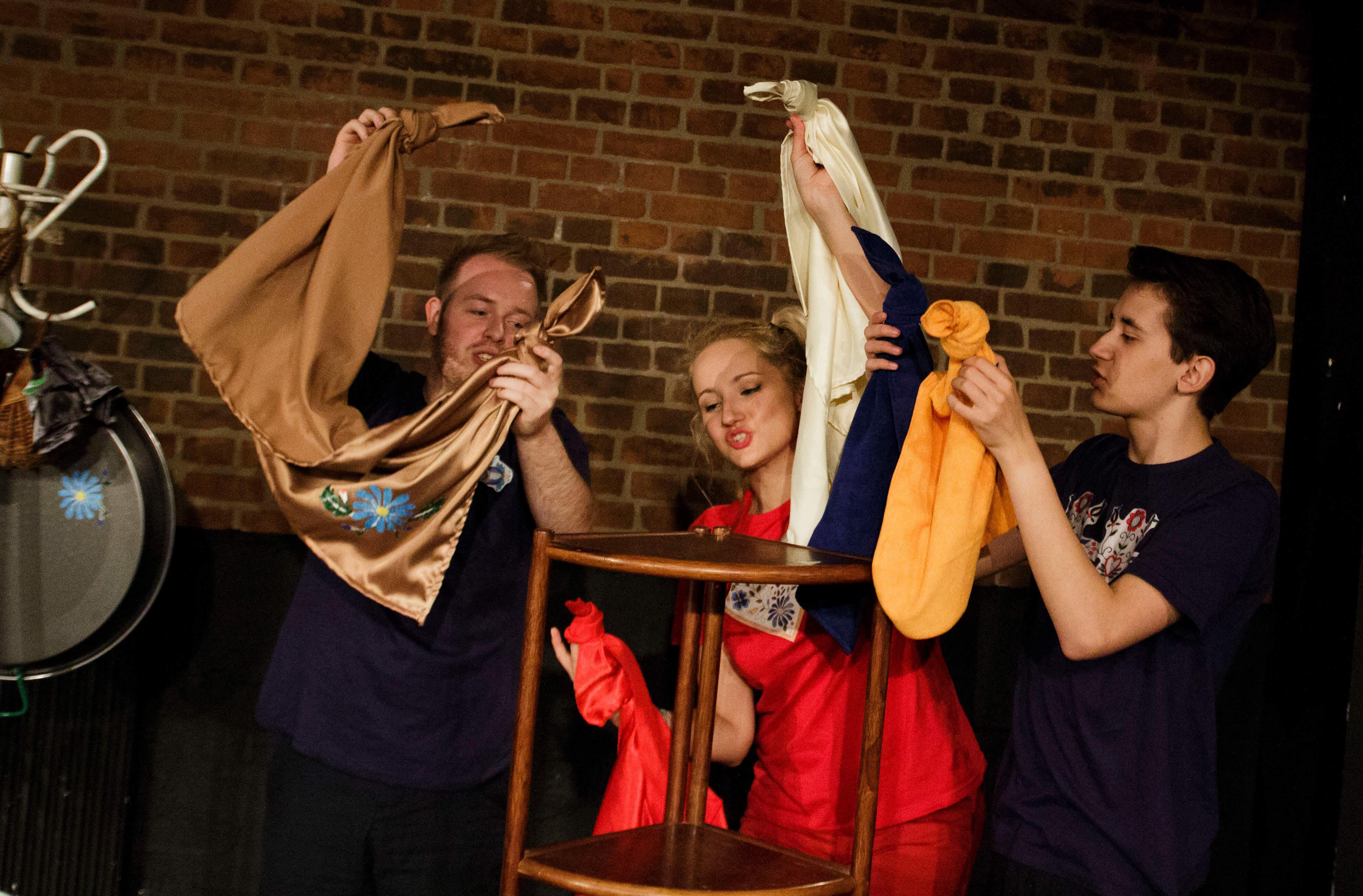 Zdjęcie ze spektaklu Tymoteusz Rym Cim Cim. Trójka aktorów trzyma w rekach kolorowe szmatki imitujace ptaki.