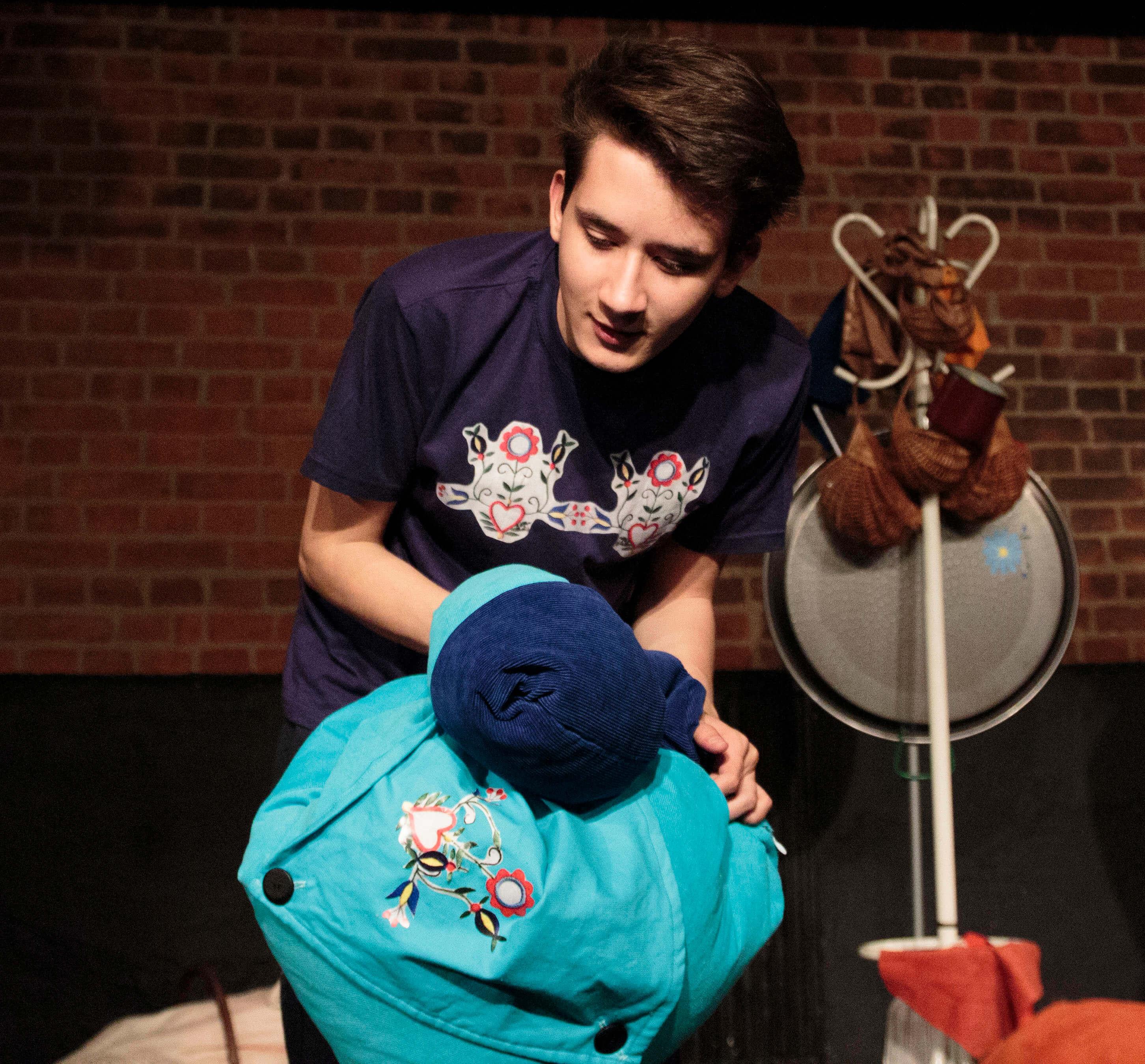 Zdjęcie ze spektaklu Tymoteusz Rym Cim Cim. Aktor w granatowej koszulce z kaszubskim wzorem trzyma przed sobą niebieska poduszkę.
