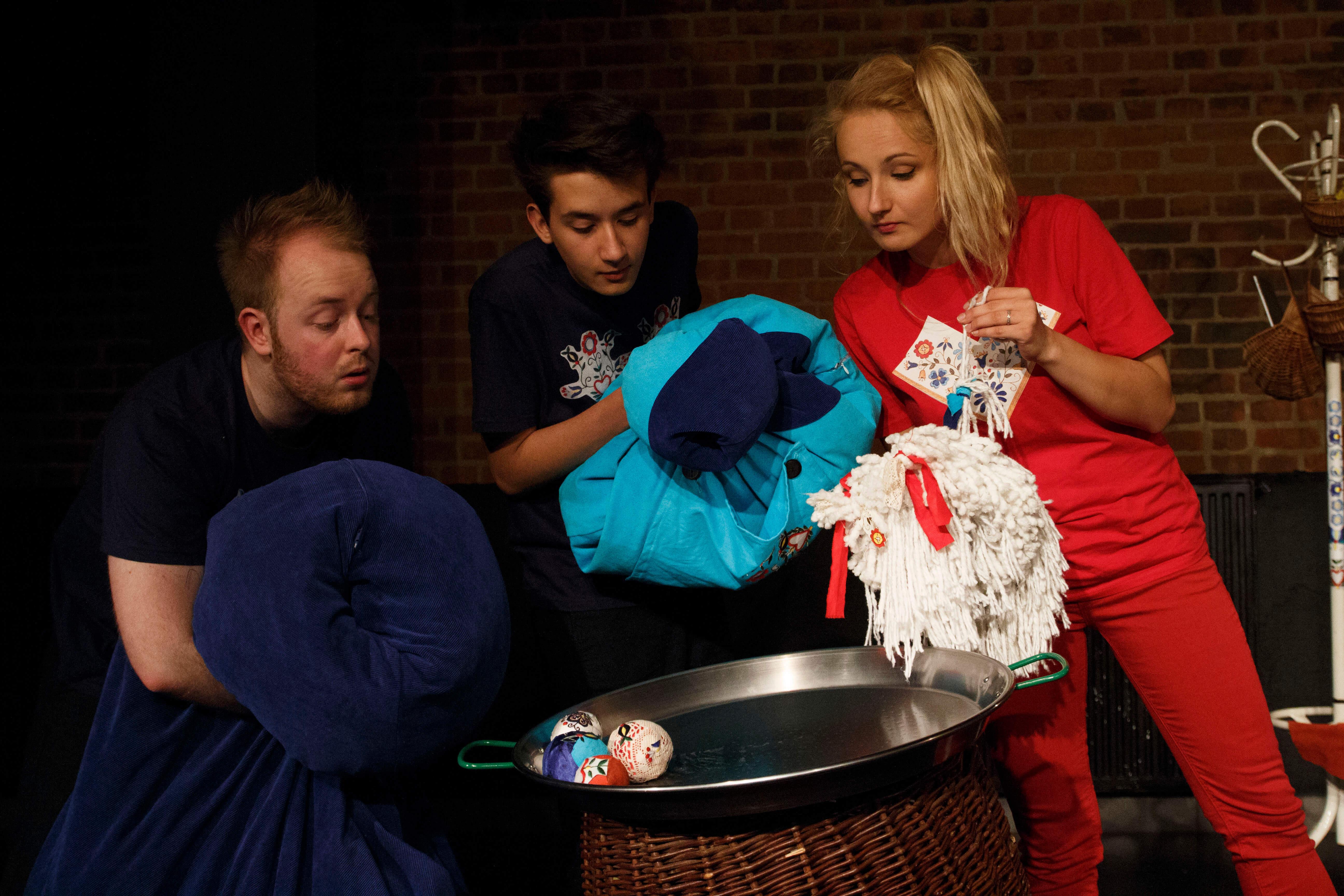 Zdjęcie ze spektaklu Tymoteusz Rym Cim Cim. Trójka aktorów pochyla się nad dużą patelnią. Trzymają w rekach niebieskie poduszki oraz biały mop. Aktorka jest ubrana w czerwony kostium.