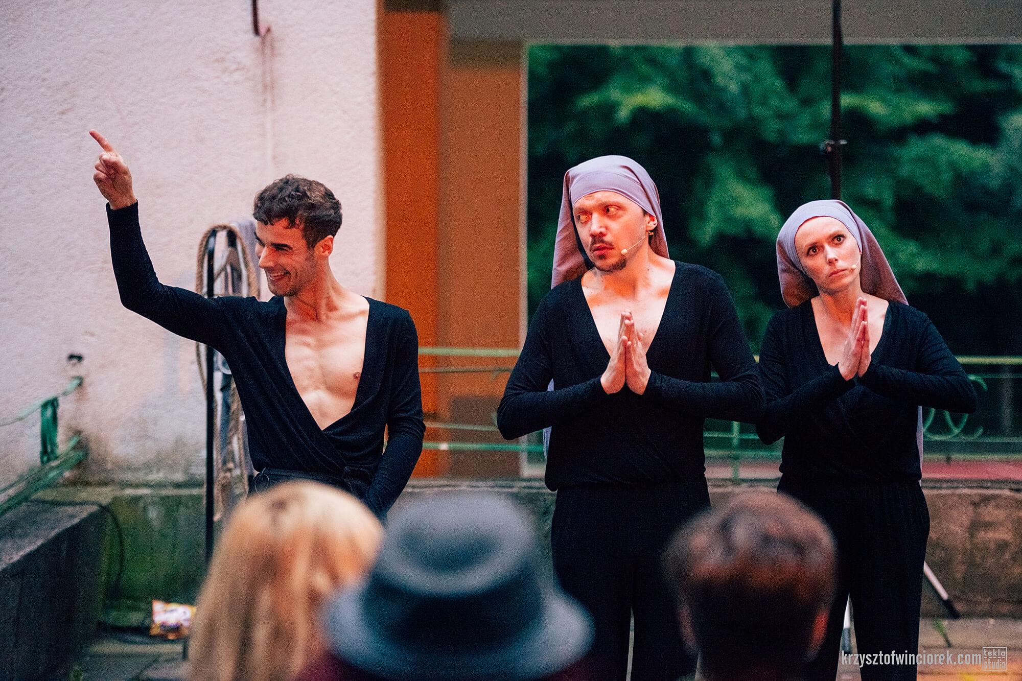 Zdjęcie z festiwalu Pociąg do miasta. Trójka aktorów. Po prawo aktor i aktorka przebrani za zakonnice z rekoma złozonymi przed sobą. Po lewo aktor z uniesiona reką.