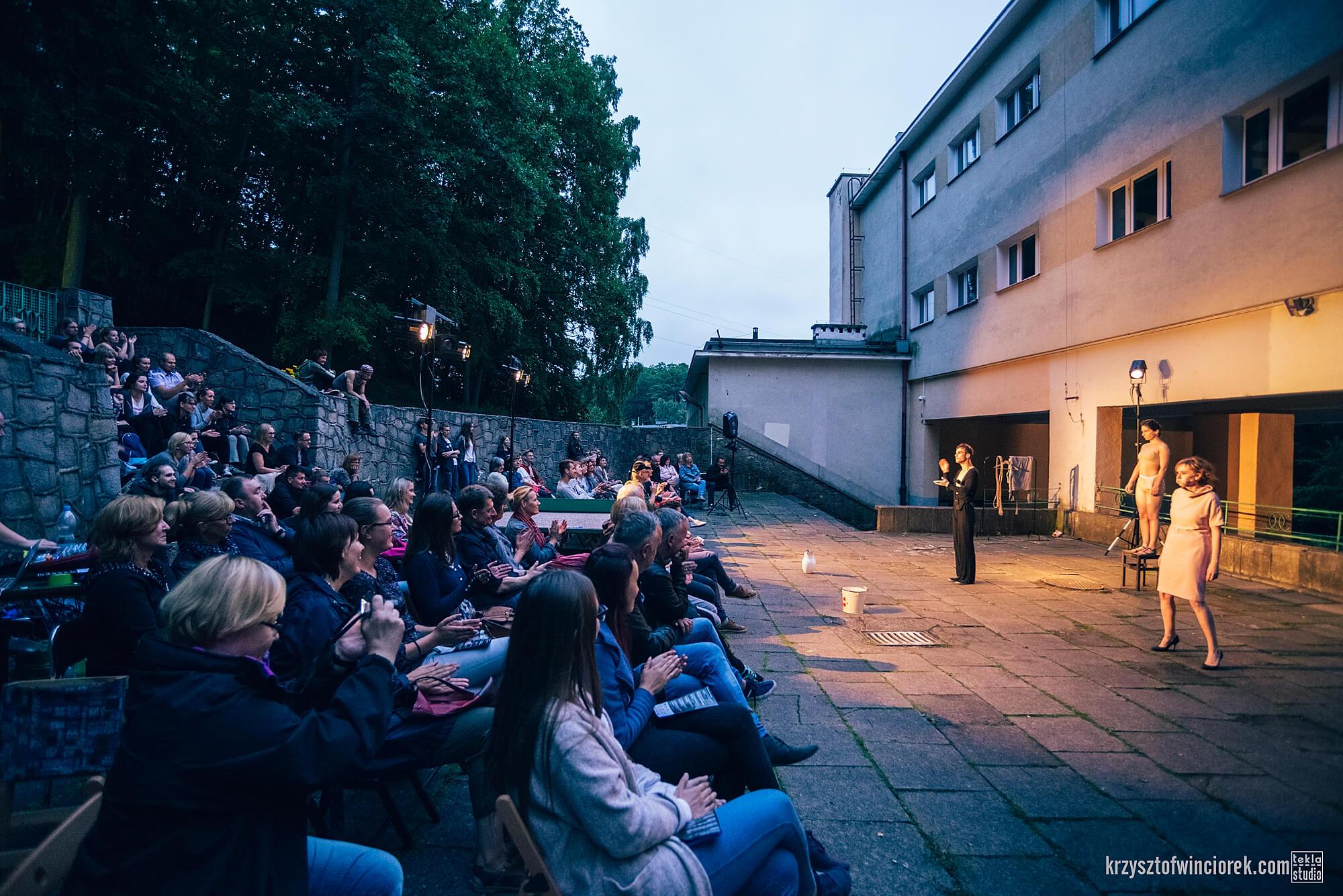 Zdjęcie z festiwalu Pociąg do miasta. Publiczność zgromadzona na schodach przy szkole. Na przeciwko nich trójka aktorów.