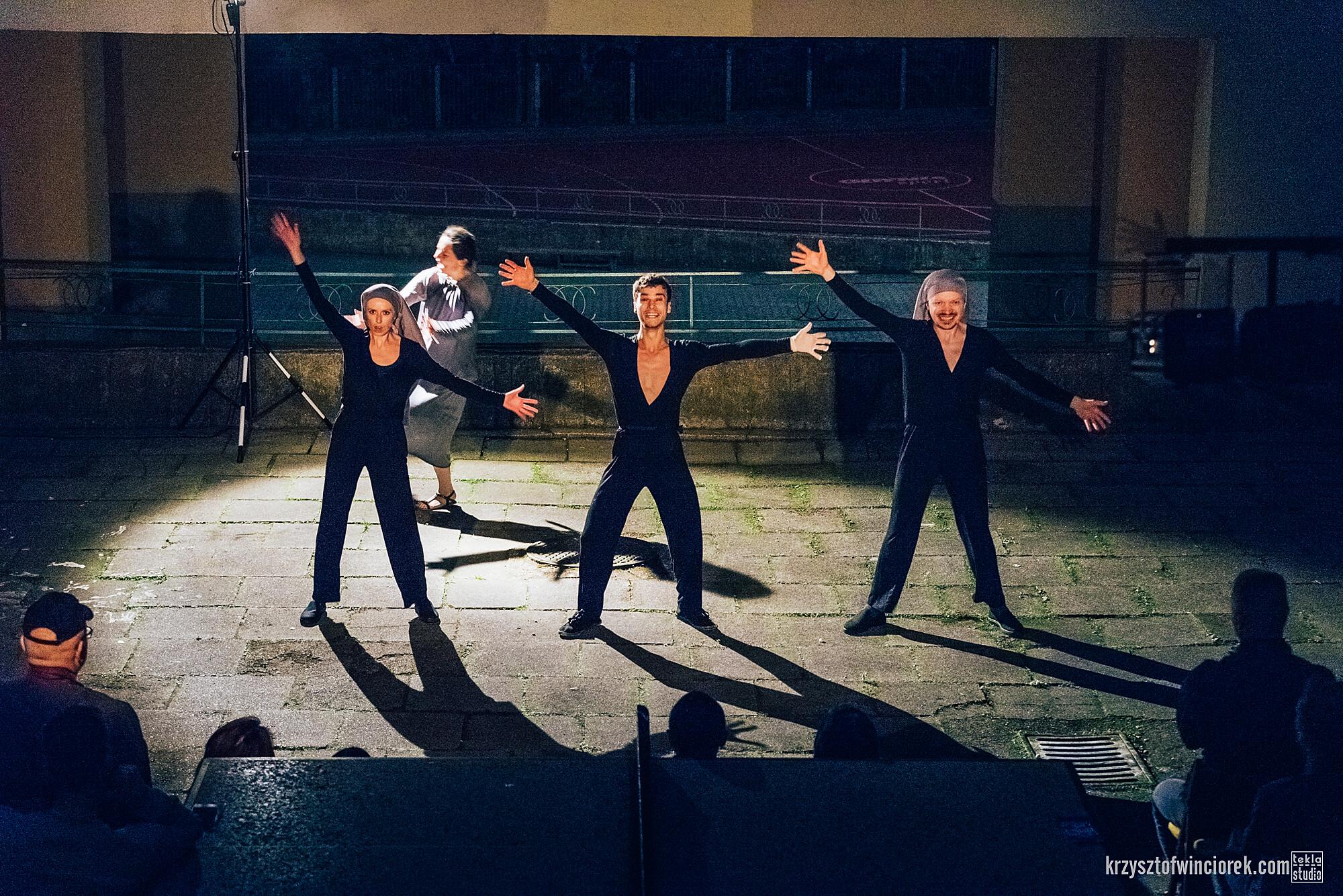 Zdjęcie z festiwalu Pociąg do miasta. Trójka aktorów ubranych na czarno z rozłozonymi na boki rękoma.