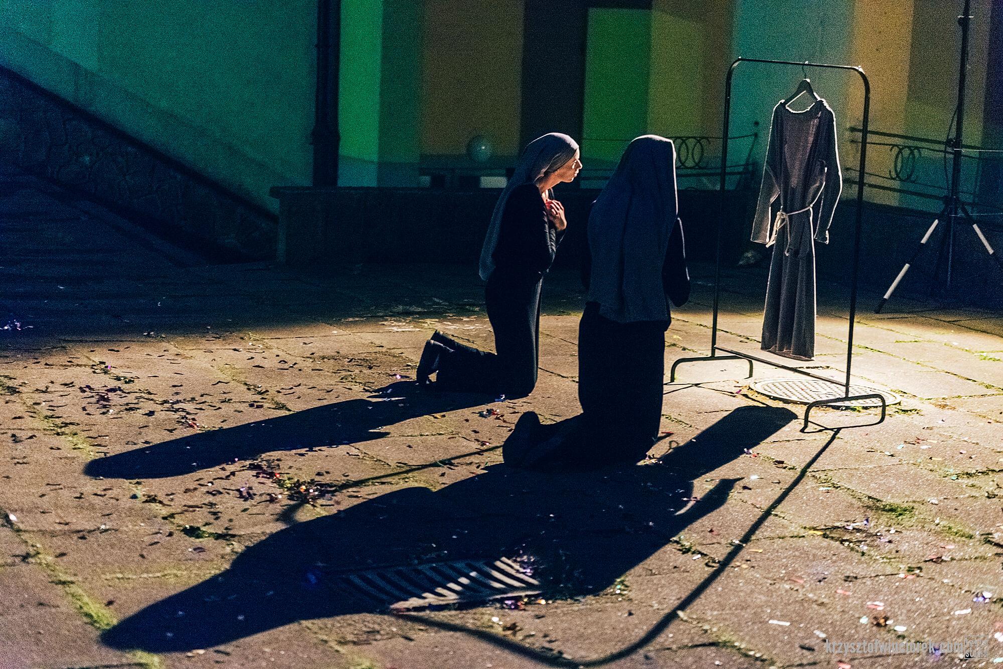 Zdjęcie z festiwalu Pociąg do miasta. Dwoje aktorów przebranych za zakonnice klęczy przed habitem wiszącym na wieszaku.