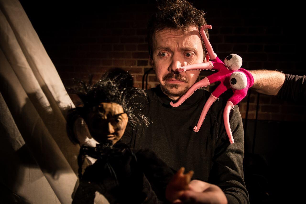 Zdjęcie do spektaklu Dzielny Kapitan Ahab. Aktor o przerazonej minie, którego atakuje rózowa ośmiornica zrobiona z rękawiczki.