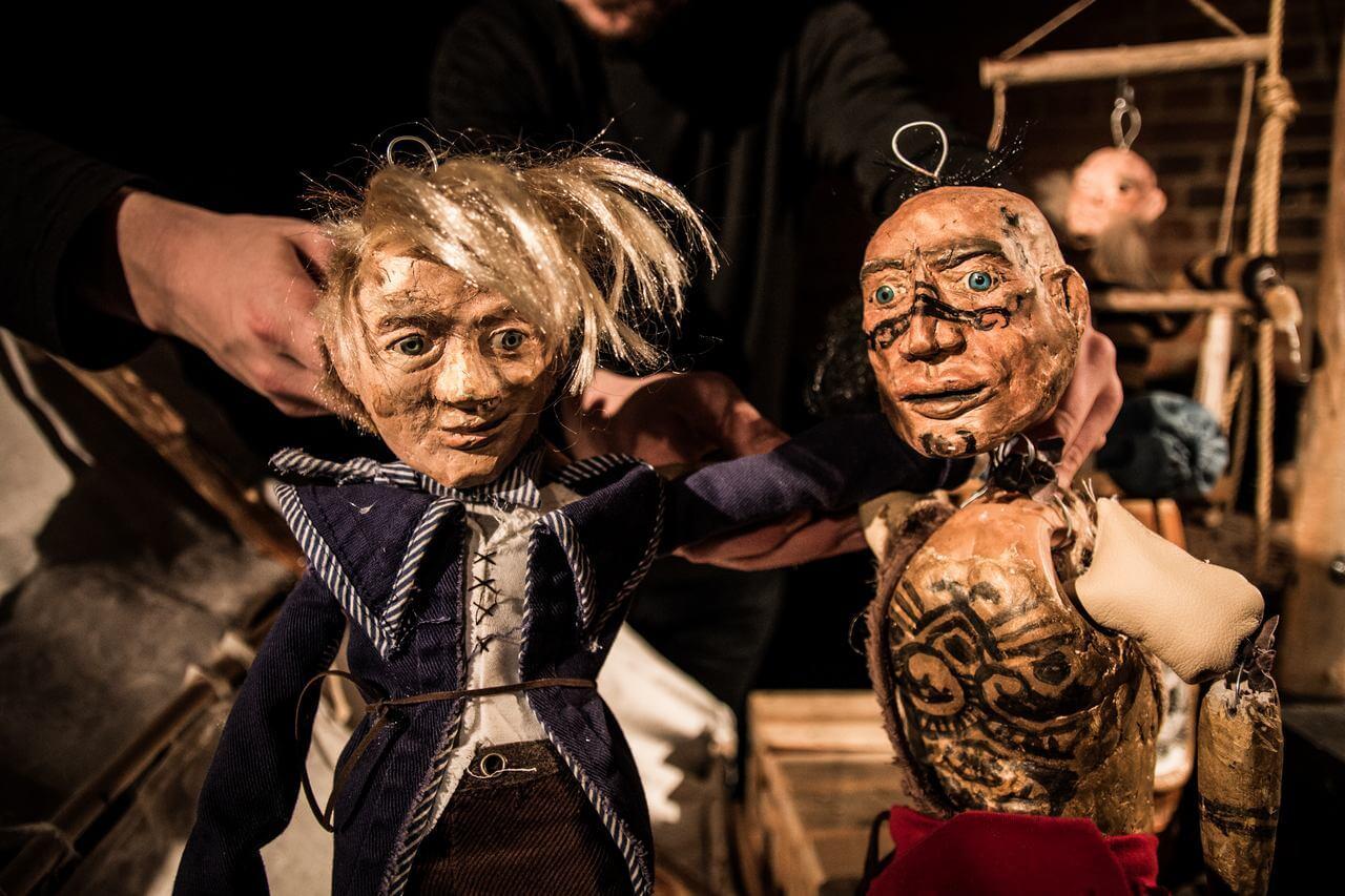 Zdjęcie do spektaklu Dzielny Kapitan Ahab. Na zdjęciu dwie lalki chłopca o potarganych blod włosach oraz wytatuowanego wojownikach.