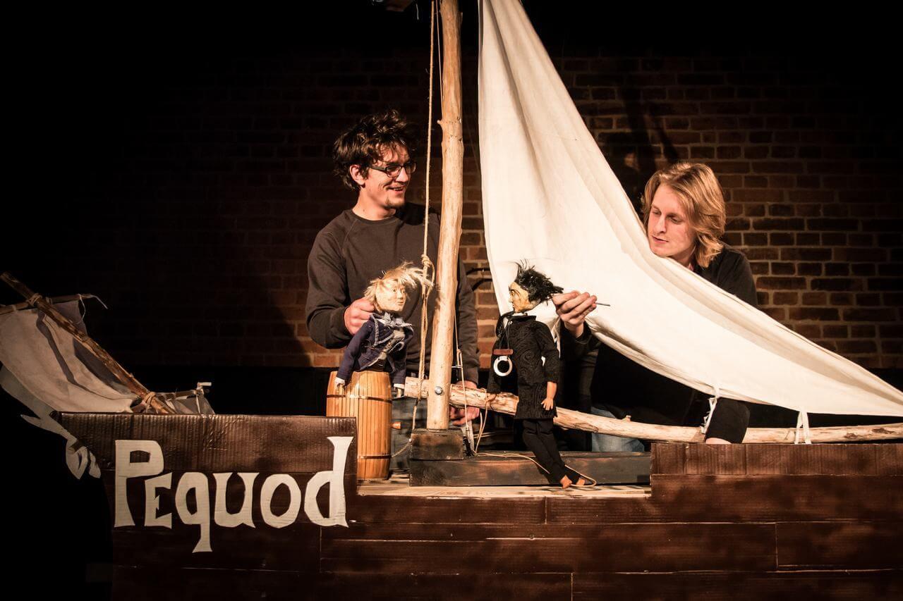 Zdjęcie do spektaklu Dzielny Kapitan Ahab. Aktorzy stoją przy makiecie statku z żaglem i animują na nim dwie lalki.