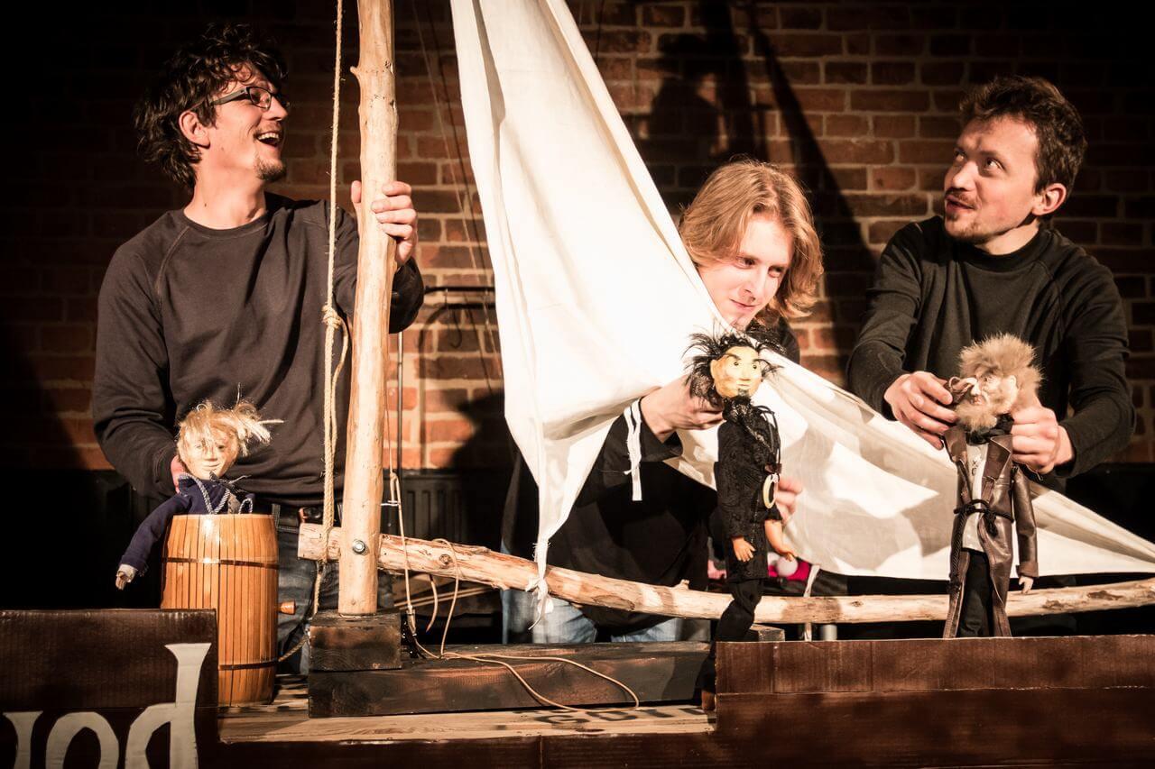 Zdjęcie do spektaklu Dzielny Kapitan Ahab. Trzech aktorów stoi przy makiecie statku z żaglem i animuje lalki - załogę statku.