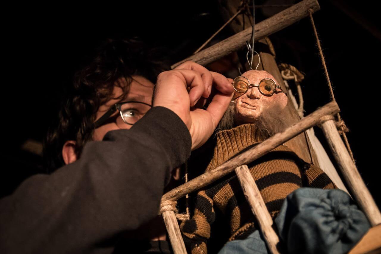 Zdjęcie do spektaklu Dzielny Kapitan Ahab. Przedstawia lalkę łysej postaci w swetrze w paski, siedzącej w drewnianej konstrukcji. Aktor zakłada jej na twarz malutkie okulary.