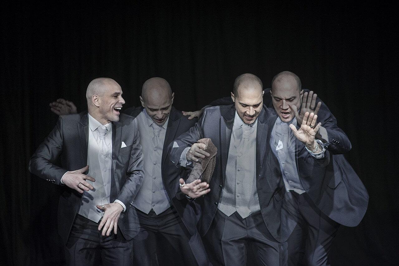 Zdjęcie ze spektaklu Without Music I Am Nothing. Dóch tancerzy w szarych garniturach w tańcu. ich wizerunki się dublują i przenikają.