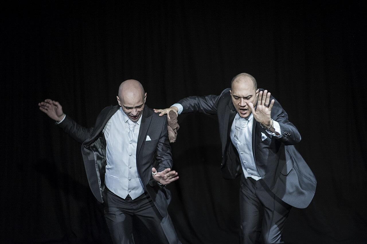 Zdjęcie ze spektaklu Without Music I Am Nothing. Dwóch tancerzy w szarych garniturach w tańcu.