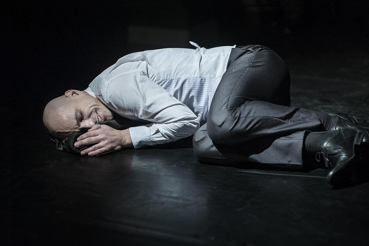 Zdjęcie ze spektaklu Without Music I Am Nothing. Aktor lezy na podłodze i się usmiecha.