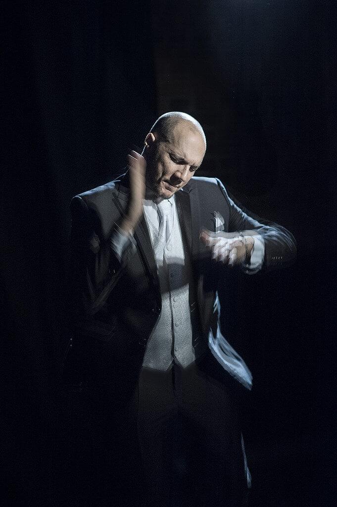 Zdjęcie ze spektaklu Without Music I Am Nothing. Tancerz porusza rękami jakby grał na bębnie.